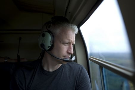 Anderson Cooper  riding in a helicopter for Planet in Peril Part I.
