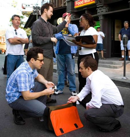 "J.J. Abrams Producer  (kneeling, left), director Matt Reeves (standing, center) and producer Bryan Burk (kneeling, right) on the set of ""Cloverfield."" Photo Credit: Sam Emerson. © 2008 by Paramount Pictures. All Rights Reserved."