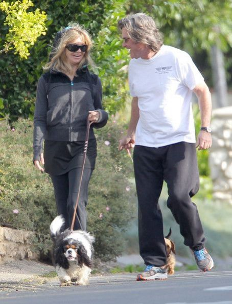 Goldie Hawn and Kurt Russell sharing a kiss while walking their dogs in Pacific Palisades, California on March 28, 2012